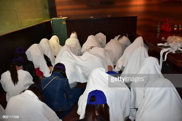 This photograph taken by Thailand's Dailynews on January 12 2018 shows female workers at 'Victoria Secret' massage parlour being detained after...