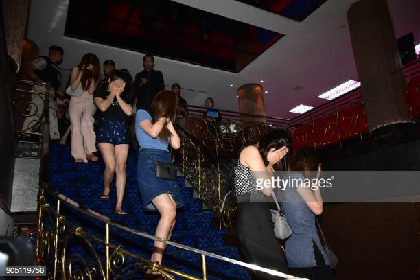 This photograph taken by Thailand's Dailynews on January 12 2018 shows female workers from 'Victoria Secret' massage parlour covering their faces...