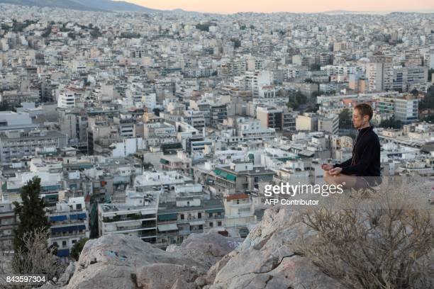 This photograph taken early September 7 shows man practicing meditation on La Pnyx Hill in Athens / AFP PHOTO / ludovic MARIN