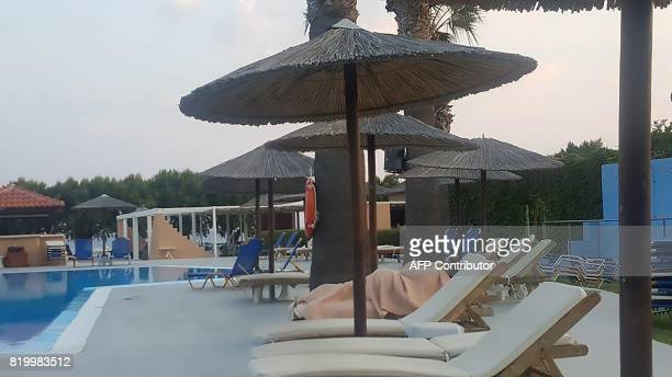 This photograph taken from a cell phone shows a woman covered in a blanket at the Marmara ClubHotel following an earthquake in Theologos Greece about...