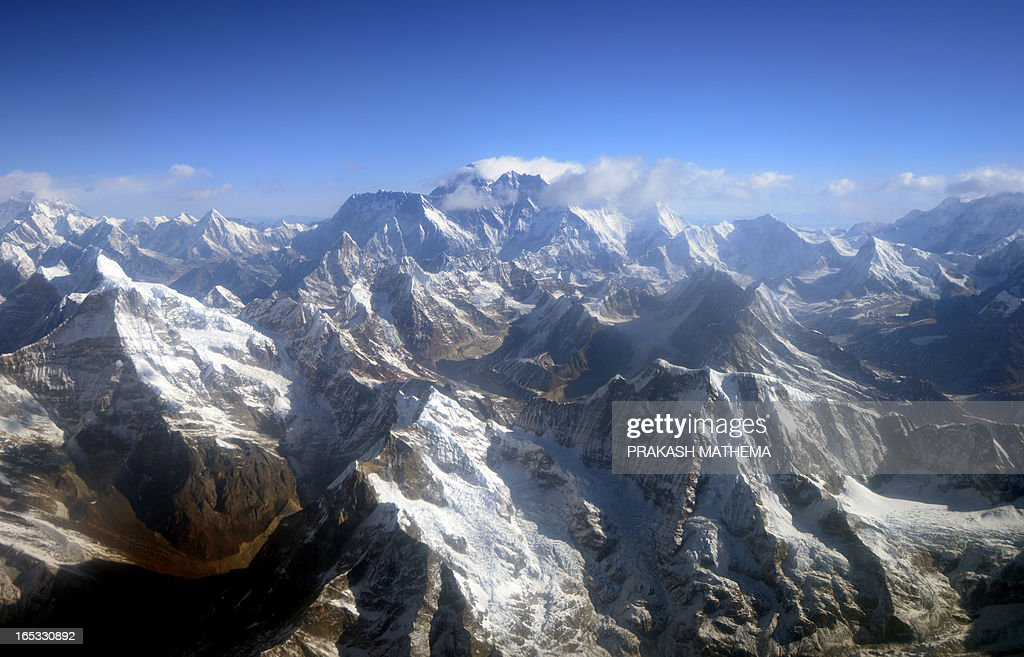 This photograph taken from an aircraft shows an aerial view of Mount Everest (C) and The Himalayan mountain range, some 140kms (87 miles) north-east of Kathmandu on April 3, 2013, on the 80th anniversary of the first manned flight over Mount Everest, the world's tallest mountain. This year is the 60th anniversary of the first summit of the 8848-metre peak. AFP PHOTO/Prakash MATHEMA