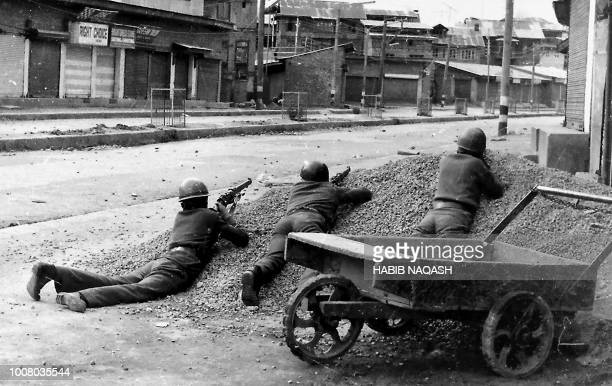 This photograph taken in 1989 shows Indian policemen taking positions after Kashmiri militants opened fire on government forces in the old city area...