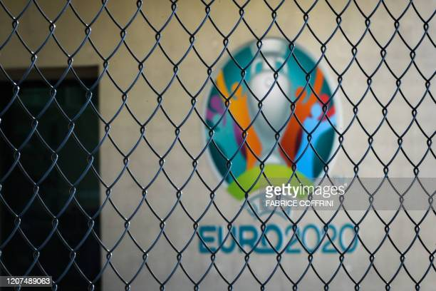 TOPSHOT This photograph taken in Nyon on March 17 shows the Euro 2020 logo behind a fence at the headquarters of UEFA the European football's...