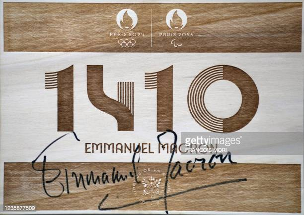 This photograph taken in Saint-Denis, outside Paris, on October 14, 2021 shows the plaque sign by French President Emmanuel Macron, marking his visit...