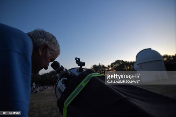 This photograph taken late August 3 shows a man using a telescope beside the observatory at Tauxigny in Central France