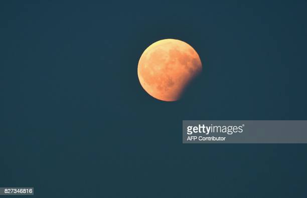 This photograph taken late August 7 shows a partial lunar eclipse as seen from in Nice southern France / AFP PHOTO / YANN COATSALIOU