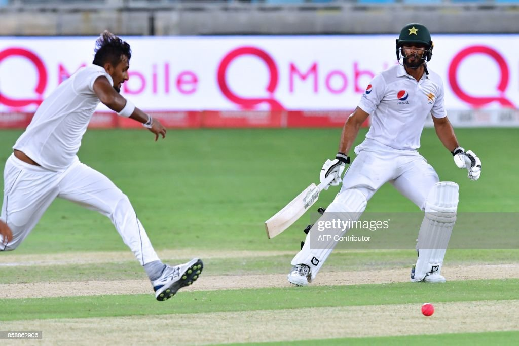 This photograph taken Ocotber 7, 2017 shows Shan Masood (R) of Pakistan running between wickets during the second day of the second Test cricket match between Sri Lanka and Pakistan at Dubai International Stadium in Dubai. /