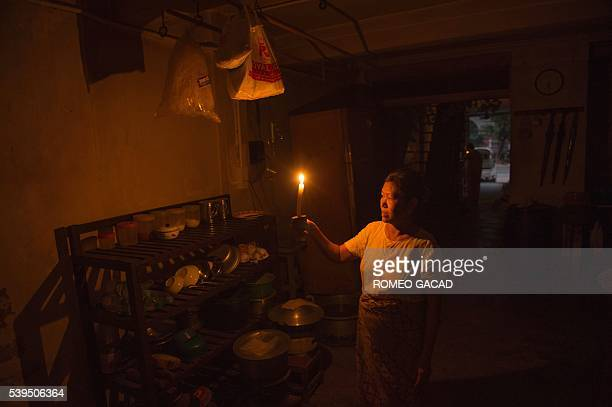 This photograph taken on April 2 shows third generation resident Aye Aye Mar lighting a candle after a power outage in her apartment in the colonial...