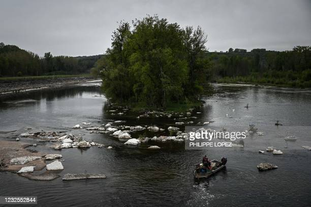 This photograph taken on April 20, 2021 shows French fishermen on a boat as they fish sheatfish on the Dordogne river near Mauzac-et-Grand-Castang. -...