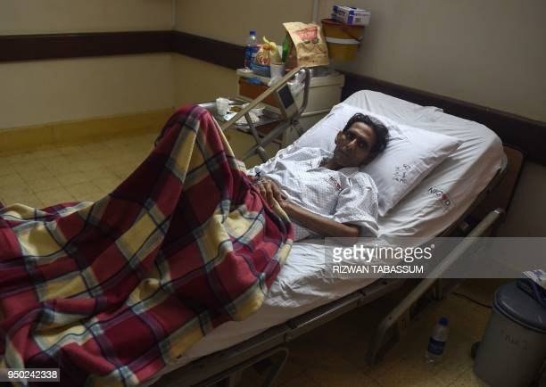 This photograph taken on April 22 2018 shows Pakistani former field hockey goalkeeper Mansoor Ahmed being treated at a hospital in Karachi following...