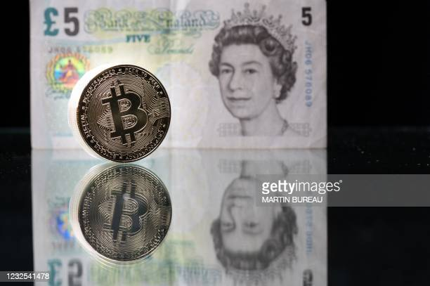 This photograph taken on April 26, 2021 in Paris shows a physical imitation of the Bitcoin crypto currency pictured with a British five pound bank...