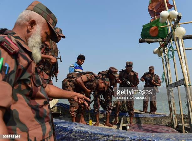 TOPSHOT This photograph taken on April 6 2018 shows Bangladesh Border Guard personnel searching a fishing boat during their patrol along the Naf...