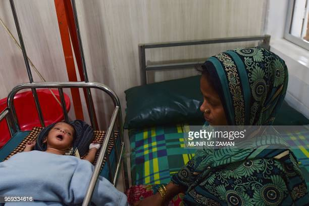 This photograph taken on April 9 shows a Rohingya mother sitting next to her sick child who is treated at a Doctors Without Borders clinic at...