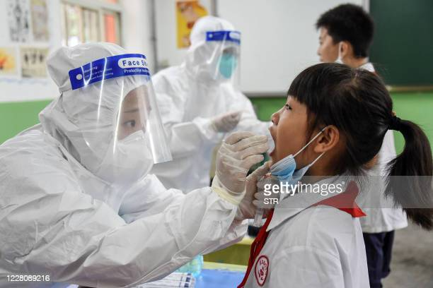 This photograph taken on August 17, 2020 shows a medical worker taking a swab sample from an elementary school student, to be tested for the COVID-19...