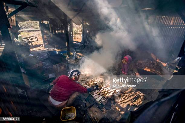 TOPSHOT This photograph taken on August 21 2017 shows people smoking fish in Surabaya in East Java province / AFP PHOTO / JUNI KRISWANTO