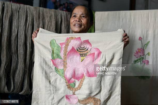 This photograph taken on August 26, 2020 shows Vietnamese weaver, Phan Thi Thuan posing for a photograph with her hand-made flower designed fabric...