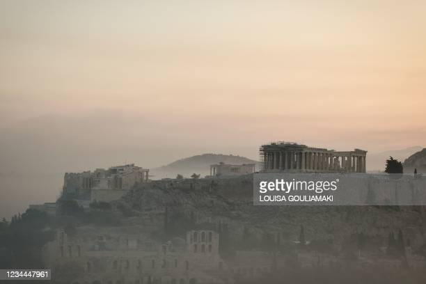 This photograph taken on August 4, 2021 shows smoke covering Athens centre and the Acropolis, due to fires burning at the foot of Mount Parnes, 30...