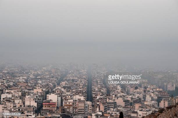 This photograph taken on August 4, 2021 shows smoke covering Athens centre, due to fires burning at the foot of Mount Parnes, 30 kilometres north of...