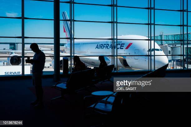 This photograph taken on August 6 shows travellers and an Air France Airbus A380 aircraft at RoissyCharles de Gaulle Airport north of Paris