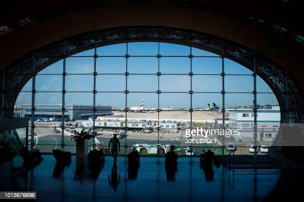 This photograph taken on August 7 shows travellers in Terminal 2E at RoissyCharles de Gaulle Airport north of Paris