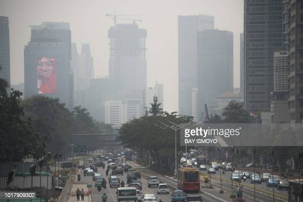 This photograph taken on August 8 2018 shows a 2018 Asian Games promotional billboard on a building as seen past traffic and haze from air pollution...