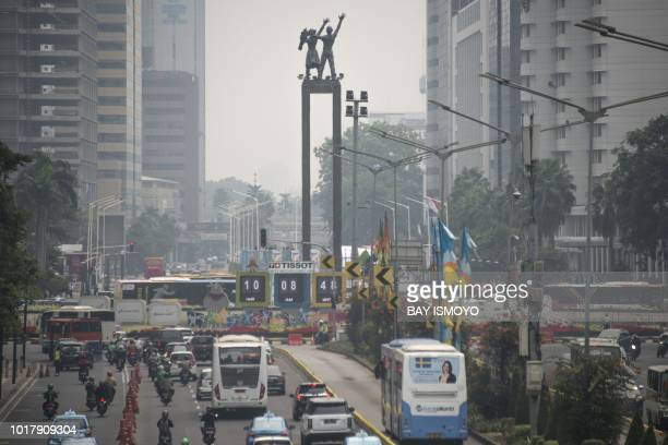 This photograph taken on August 8 2018 shows the 2018 Asian Games countdown board as seen past traffic and haze from air pollution in Jakarta's city...
