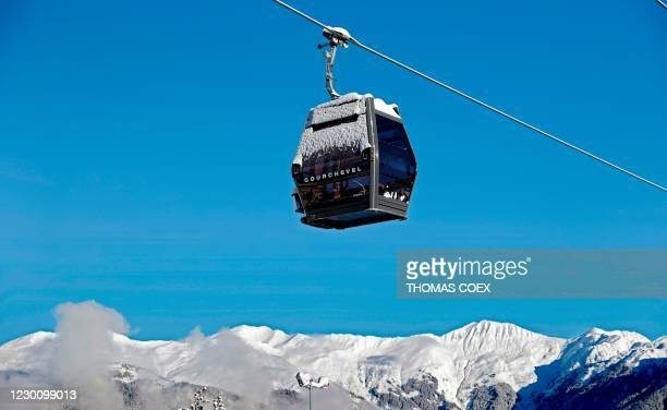This photograph taken on December 13, 2020 shows a cable car at a standstill above a ski slope in the Alps resort of Courchevel. - Due to the...