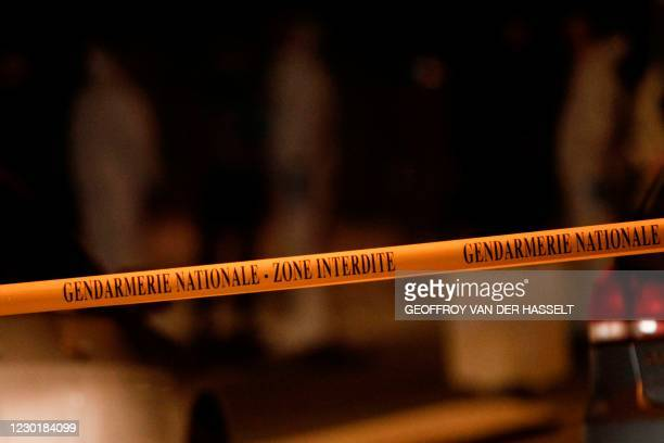 This photograph taken on December 17, 2020 shows a gendarmerie tape as French gendarmes and forensic officers work next to cars as the road is...