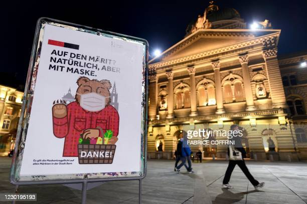 """This photograph taken on December 18, 2020 shows a poster reading in German: """"On the market? Of course but with mask"""" in Bern after the annoucement..."""