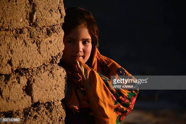 This photograph taken on December 20 2015 shows an Afghan girl as she stands outside her home at sunset on the outskirts of Herat AFP PHOTO / Aref...