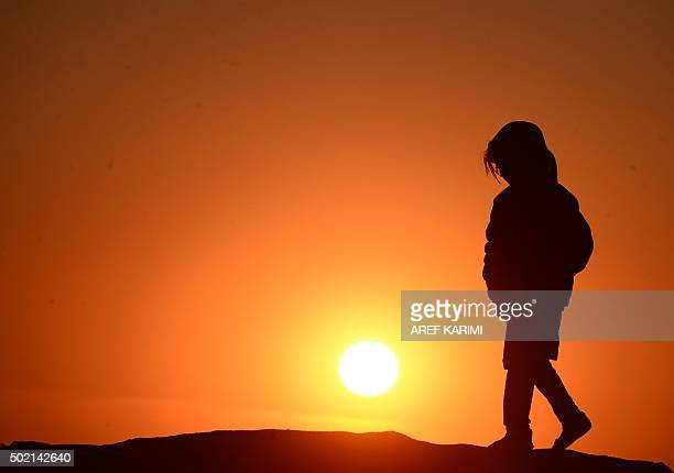 TOPSHOT This photograph taken on December 20 2015 shows an Afghan girl walking outside her home during sunset on the outskirts of Herat AFP PHOTO /...