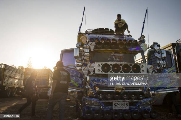 This photograph taken on December 23 2017 shows men hanging out next to their truck decorated with Michelin Man dolls and loudspeakers a fancy truck...