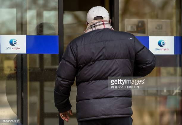 This photograph taken on December 28 shows a pedestrian walking into a Job Centre in Lille northern France French President Emmanuel Macron has come...
