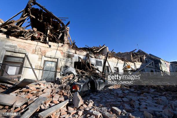 This photograph taken on December 29 shows the wreckage of a car and damaged buildings in Petrinja, some 50kms from Zagreb, after the town was hit by...