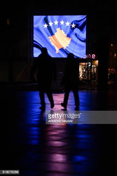 This photograph taken on February 10 shows people walking by a screen featuring Kosovo flag in Pristina Kosovo which celebrates the tenth anniversary...