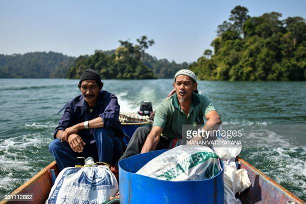 This photograph taken on February 11 2018 shows traditional Malaysian honey hunters Zaini Abdul Hamid and Abdul Samad Ahmad travelling on a boat...