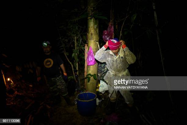 This photograph taken on February 11 2018 shows traditional Malaysian honey hunter Zaini Abdul Hamid covering his face with multiple cloth layers...