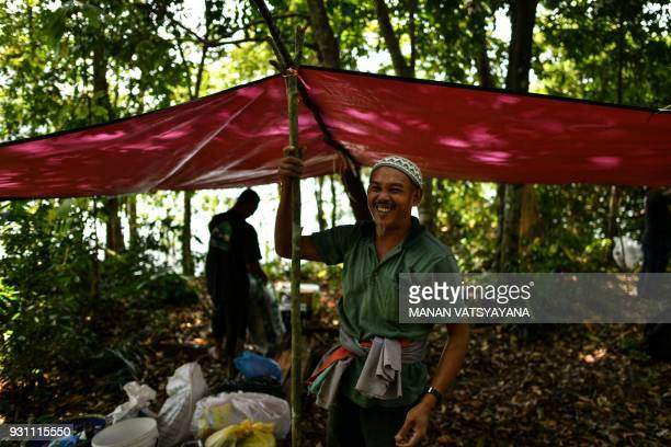 This photograph taken on February 11 2018 shows traditional Malaysian honey hunters Zaini Abdul Hamid smiling after setting up a base tent to harvest...