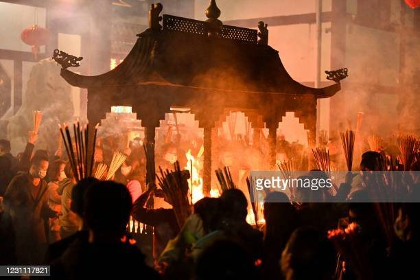 This photograph taken on February 11, 2021 shows people burning incense and praying for good luck on the eve of the Lunar New Year at a temple in...