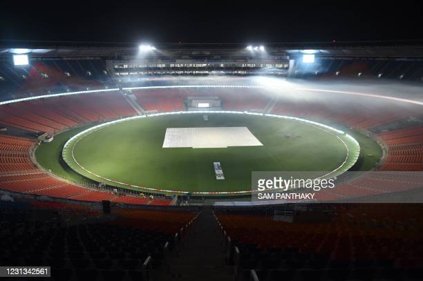 This photograph taken on February 23, 2021 shows fogging underway as a precautionary measure at the Sardar Patel Stadium, the world's biggest cricket...