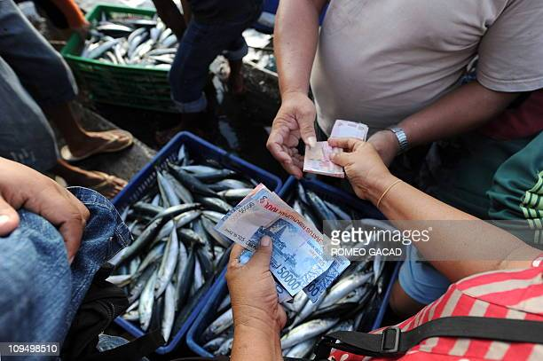 This photograph taken on February 24, 2011 shows buyers purchasing freshly caught fish at Bitung town fishport in North Sulawesi province. Bitung is...