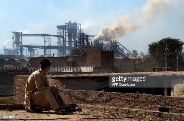 This photograph taken on February 25 shows a Pakistani worker watching smoke rising from factories on the outskirts of the northwestern city of...