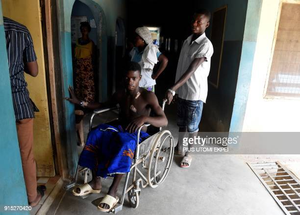 This photograph taken on February 3 shows a victim of violence at Gboko bus station as he is pushed in a wheelchair for treatment at a private...