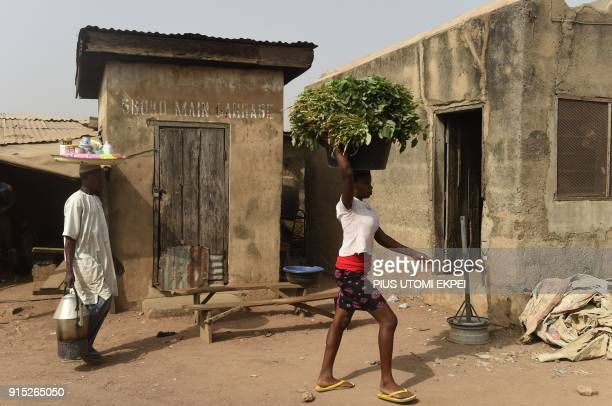 This photograph taken on February 3 shows vendors as they walk past the main garage office at Gboko bus station in the restive Benue State...