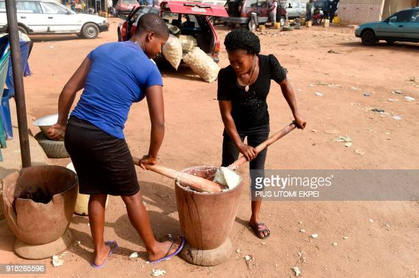 This photograph taken on February 3 shows women as they pound white yams with a mortar and pestle one of Nigeria's most popular dishes at Gboko bus...