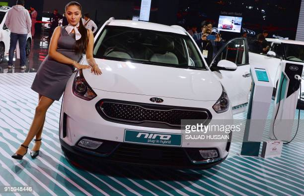 This photograph taken on February 7 2018 shows a model posing next to KIA's electric hybrid Niro car during the Indian Auto Expo 2018 in Greater...