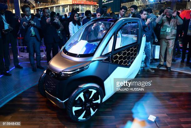 This photograph taken on February 7 2018 shows visitors looking at a Mahindra's UDO compact twoseater electric mobility pod during the'AutoExpo 2018'...