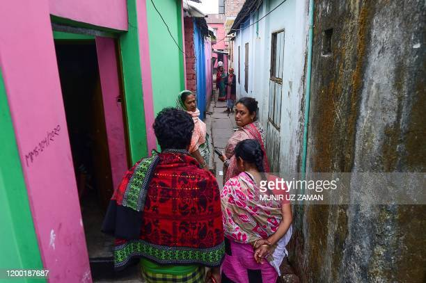 This photograph taken on February 8 2020 shows Jhumur Begum who heads a sex workers group walking with members of the group through a brothel area in...