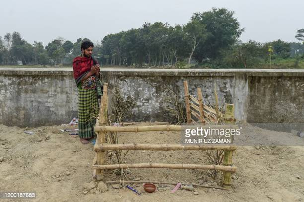 This photograph taken on February 8 2020 shows Mukul Seikh praying in front of the grave of his mother former sex worker Hamida Begum in Daulatdia in...