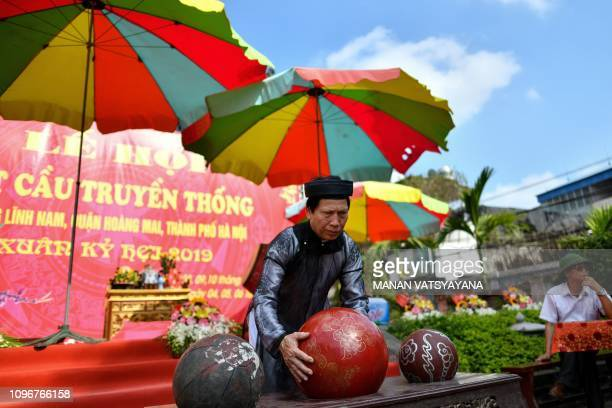 This photograph taken on February 9 2019 shows a priest arranging the prized jackfruit wooden ball before the start of the traditional 'Vat Cau' or...